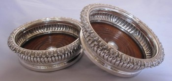 A pair of George 1V antique silver wine coasters.